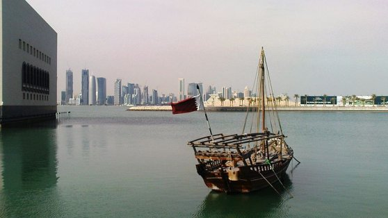 Katar - Ship with a flag of Qatar in front of the skyline of Doha (capital), next to the Museum of Islamic Art